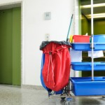 Janitorial cleaning cart in front on elevators in commercial building