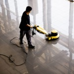 Worker using equipment to wax and buff tile flooring in commercial building